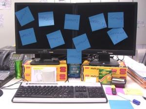 """Monitor z naklejonymi niebieskimi """"żółtymi karteczkami"""""""